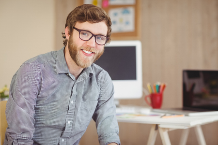 young businessman: Bearded hipster smiling at camera in his office