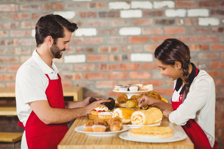 tidying up: Waiters tidying up pastries on the counter at the coffee shop