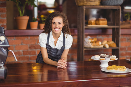 Portrait of smiling barista leaning on counter at coffee shop