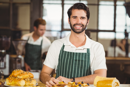 tidying up: Portrait of a waiter tidying up the pastries at the coffee shop Stock Photo