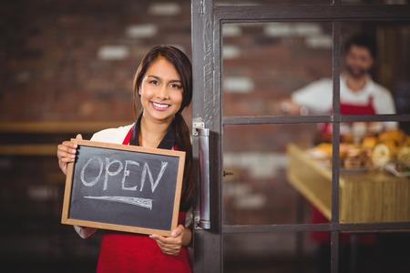 Portrait of waitress showing chalkboard with open sign at coffee shop Foto de archivo