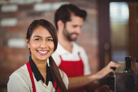 Retrato de una camarera de usar la máquina de café en la cafetería