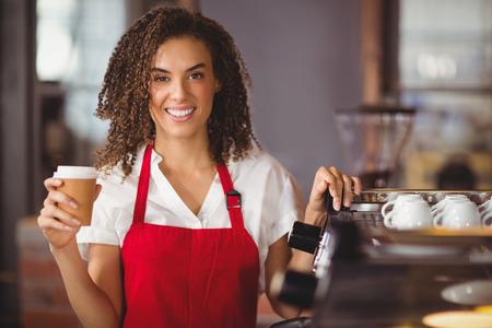 Portrait of a waitress holding a take-away mug at the coffee shop