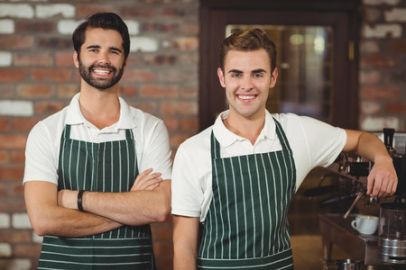 baristas: Portrait of two smiling baristas with arms crossed at the coffee shop