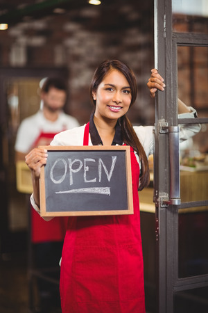 Portrait of waitress showing chalkboard with open sign at coffee shop Standard-Bild