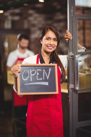 puerta abierta: Retrato de camarera mostrando pizarra con la muestra abierta en la cafetería Foto de archivo