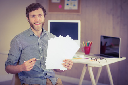 holding notes: Bearded hipster smiling at camera holding notes in his office