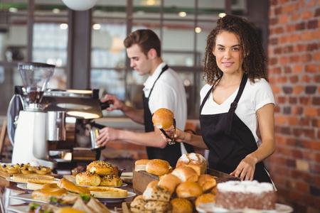 camarero: Retrato de camarera sonriente que sostiene rollo de pan con pinzas en la cafeter�a