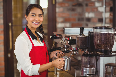 red indian: Portrait of a barista steaming milk at the coffee shop