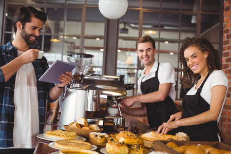 Portrait of smiling colleagues serving customer with tablet and coffee at coffee shop Imagens - 44793217