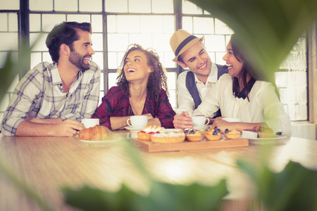 riendo: Reírse amigos disfrutando de café y golosinas en la tienda de café