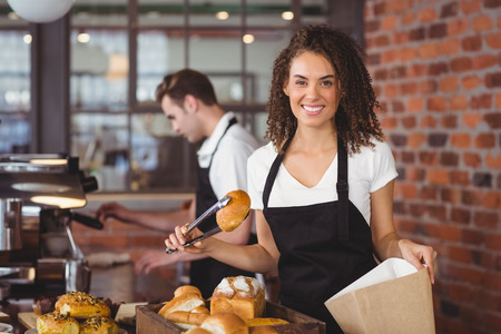 food and drink industry: Portrait of smiling waitress putting bread roll in paper bag at coffee shop