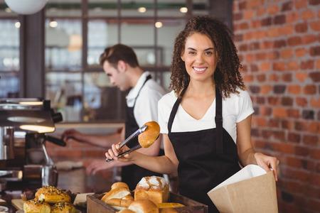mandil: Retrato de la sonrisa camarera poner bollería en bolsa de papel en la cafetería Foto de archivo