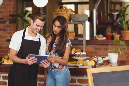 tablet: Smiling waiter showing pretty customer tablet at coffee shop
