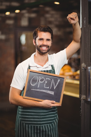 coffee shop: Portrait of a waiter showing chalkboard with open sign at the coffee shop