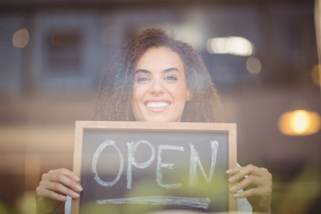 shop sign: Portrait of a waitress showing chalkboard with open sign at the coffee shop