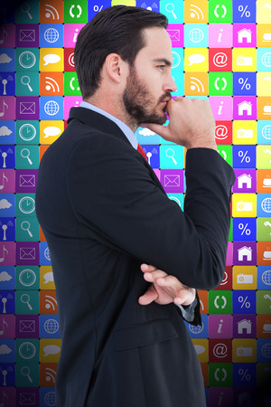 hand on the chin: Thinking businessman standing with hand on chin against app wall