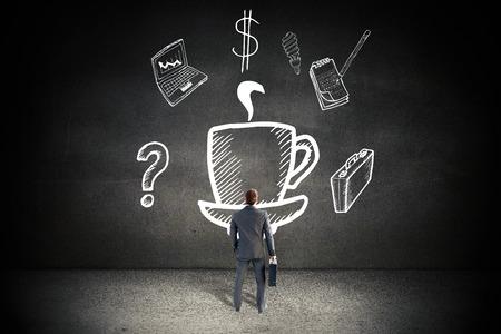 mur noir: Homme d'affaires debout avec sa serviette contre le mur noir