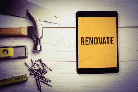 The word renovate  and tablet pc against tablet displaying blueprint
