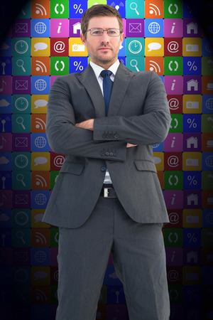 frowning: Frowning businessman looking at camera against app wall