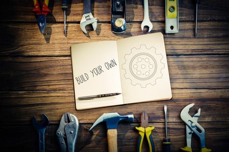 own: The word build your own and notebook and pen against blueprint