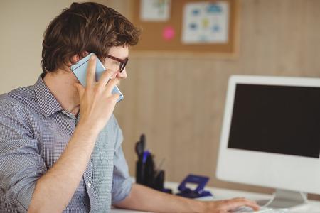 hombre de negocios: Hipster negocios en el tel�fono en el escritorio en su oficina