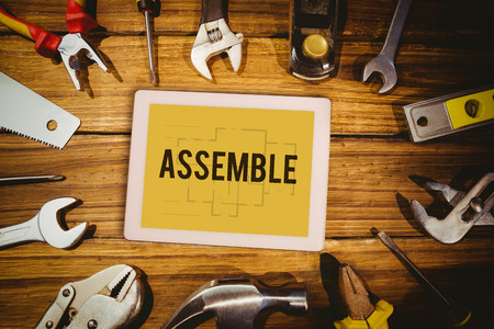 assemble: The word assemble and tablet pc against blueprint