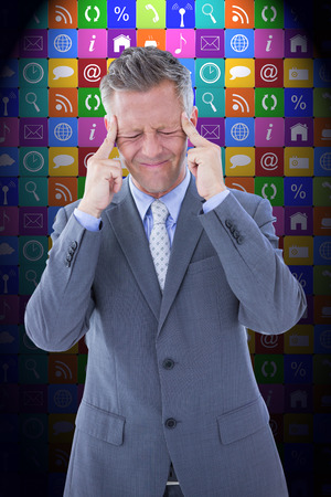 Businessman with headache against app wall Stock Photo
