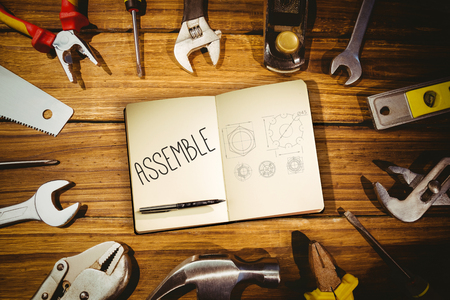 assemble: The word assemble and notebook and pen against blueprint