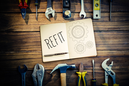 refit: The word refit and notebook and pen against blueprint Stock Photo