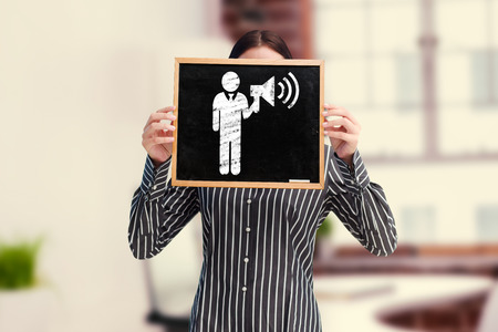 businessman using a megaphone: Businesswoman showing board against laptop on desk with glasses and notepad Stock Photo