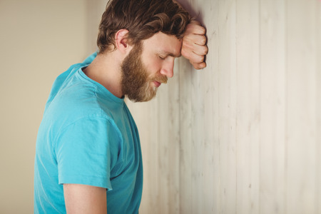 wistfulness: Troubled hipster leaning against wall in side view