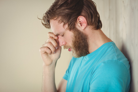 dreariness: Troubled hipster leaning against wall in side view