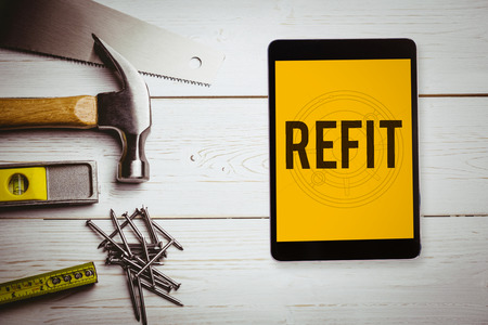 refit: The word refit and tablet pc against blueprint