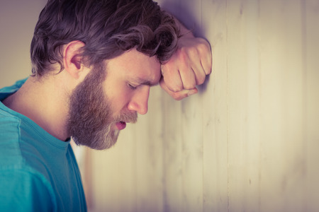 concerned: Troubled hipster leaning against wall in side view