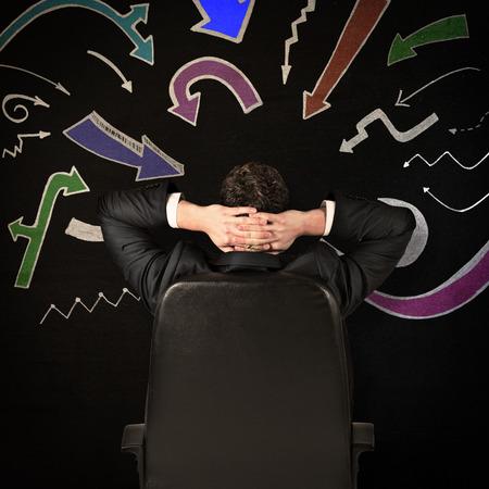 swivel chair: Businessman sitting in swivel chair  against black