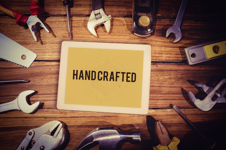 hand crafted: The word hand crafted and tablet pc against blueprint