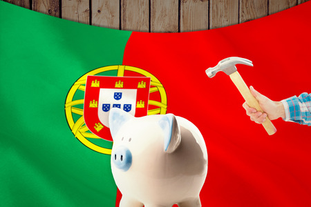 portugese: hand holding hammer against digitally generated portugese national flag