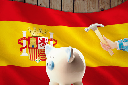 finacial: hand holding hammer against digitally generated spanish national flag Stock Photo