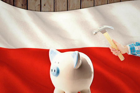 polish flag: hand holding hammer against digitally generated polish flag rippling Stock Photo