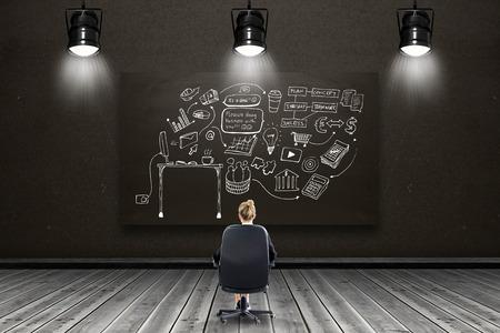 swivel chair: Businesswoman sitting on swivel chair against blackboard