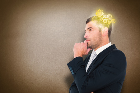 frowning: Frowning businessman thinking  against grey Stock Photo