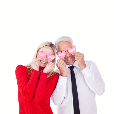 ttractive: Silly couple holding hearts over their eyes against blood donor Stock Photo