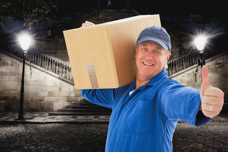 man thumbs up: Happy delivery man holding cardboard box against building by night
