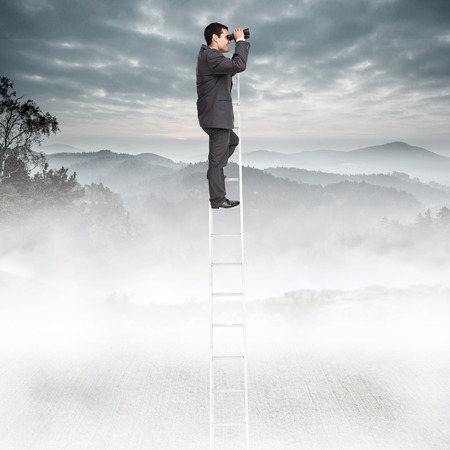 using binoculars: Businessman standing on ladder using binoculars against misty forest Stock Photo