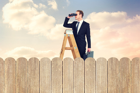 fence: Businessman looking on a ladder against purple sky over fence