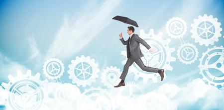 businessman jumping: Businessman jumping holding an umbrella against blue sky Stock Photo