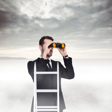 Businessman looking on a ladder against grey sky Stock Photo