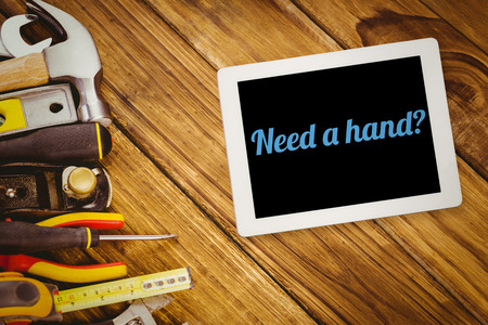 in need of space: The word need a hand? and tablet pc against desk with tools Stock Photo