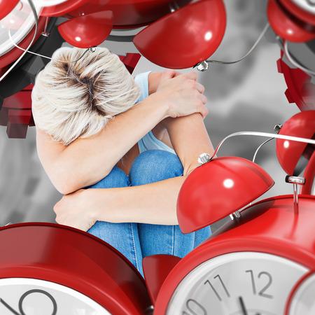 cowering: Depressed woman hiding her head  against grey vignette